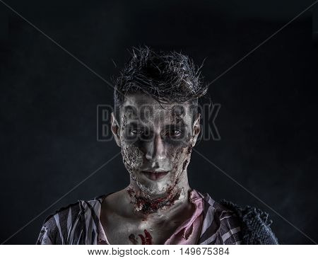 Male zombie standing on black background, turning around looking at camera. Halloween theme
