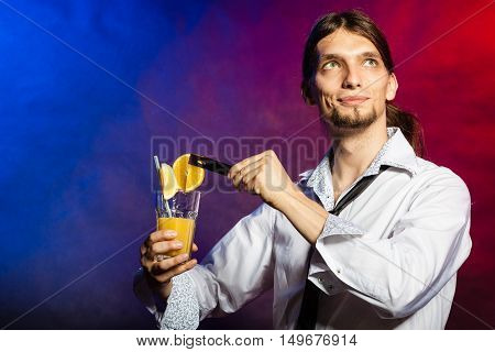 Alcohol liquor drinking relax concept. Bartender with orange drink. Young male barman holding glass.