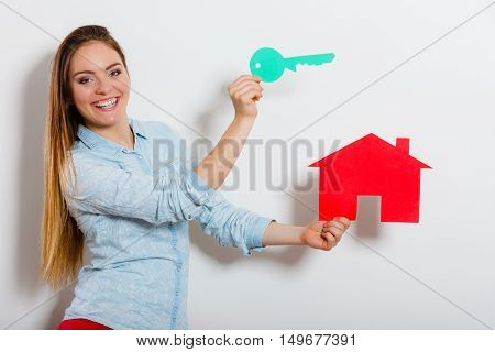 Happy young woman girl holding red paper house and key dreaming about new home house. Housing and real estate concept.