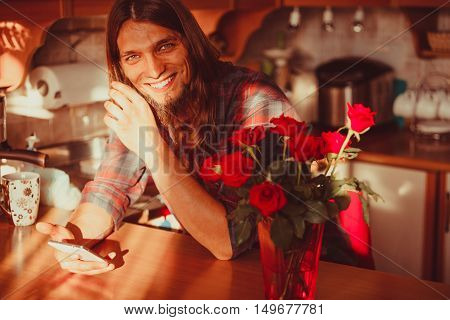 Happy Young Man With Smartphone And Roses.
