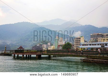 NANTOU TAIWAN - SEPTEMBER 04: view of Taiwan's famous tourist destination Sun Moon Lake scenic area. The tourist visitor center and other buildings such as hotels are in the midground on September 04th 2014 in Nantou