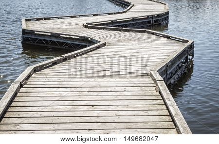 horizontal  close up image of a curving wooden walking bridge floating  the lake into the distance.