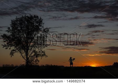 beautiful horizontal image of a silhouette of a lady wearing a dress and big hat standing close to a big tree reading a book under a gorgeous orange sunset in summer time