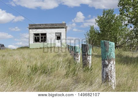 horizontal image of an old abandoned business building with fence posts sitting amidst tall grass that has not been mowed in the summer time.