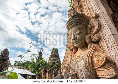 The angel guardian statue standing with the ancient pagoda in Inle lake of Myanmar.