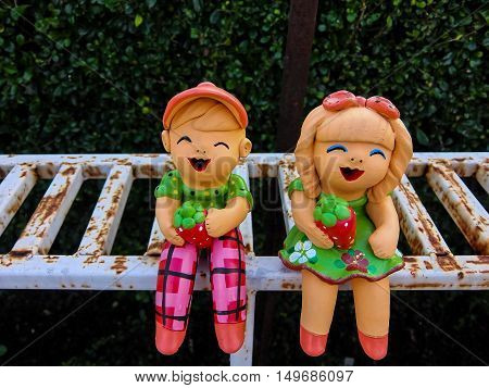 Twin clay dolls sitting for welcome in the garden