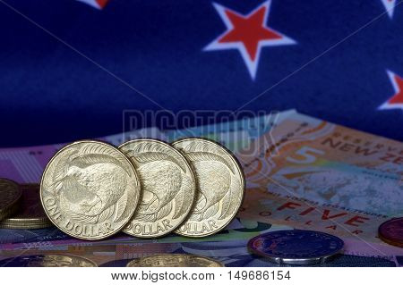 New Zealand one dollar coins, notes, coins and flag.