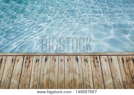 Wood Floor Beside The Blue Crystal Clear Water.