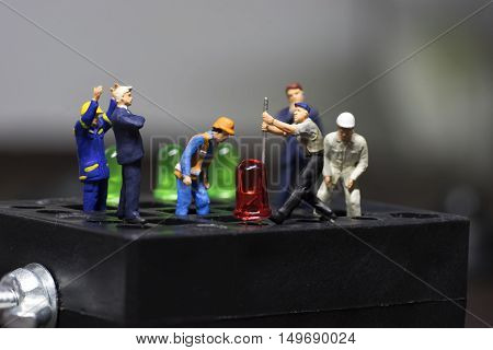 mini worker try to remove led light from black block with his boss and team - can use to display or montage on products