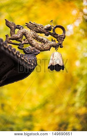 Dragon sculpture with a bell on a roof of a chinese temple with yellow leaves from autumn trees in the background