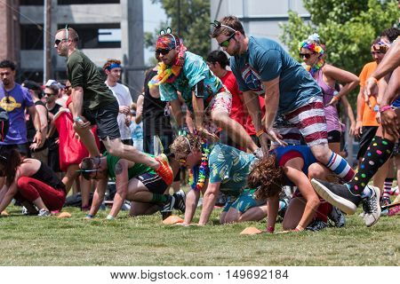 ATLANTA, GA - JULY 2016:  Men and women play leap frog one of many children's games played at the Atlanta Field Day event at the Old Fourth Ward Park in Atlanta GA on July 16 2016.