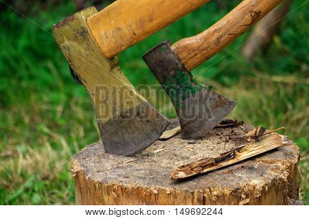 Ax in the deck on a background of green grass and firewood