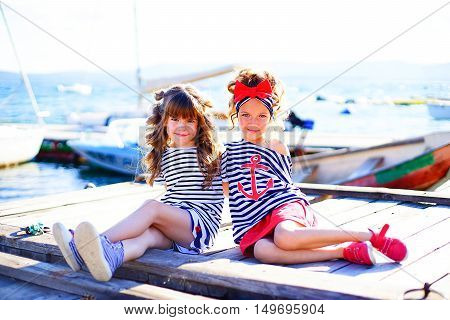 two young girls sitting on the dock laughing and smiling looking around
