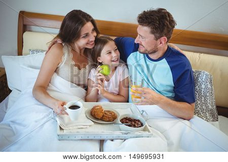 Parents sitting on bed with daughter and having breakfast at home