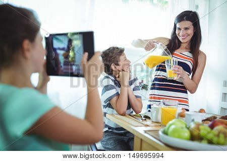 Girl clicking a photo of mother and brother from digital tablet at home