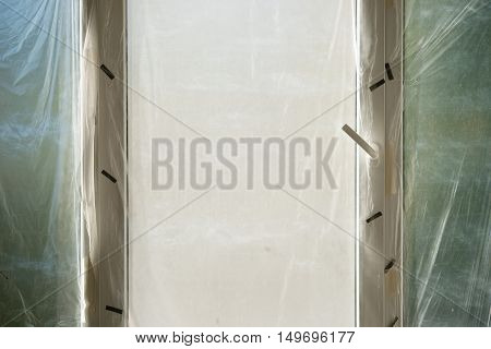 Window protected by plastic film in home renovation interior