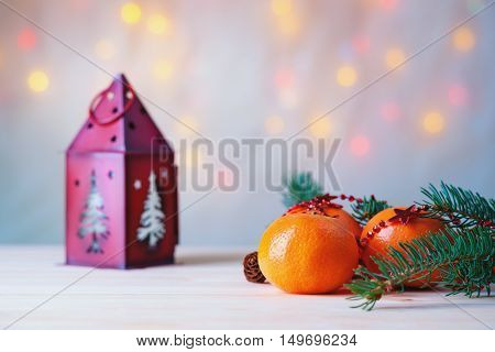 Mandarins with fir-tree branch and house shaped candlestick