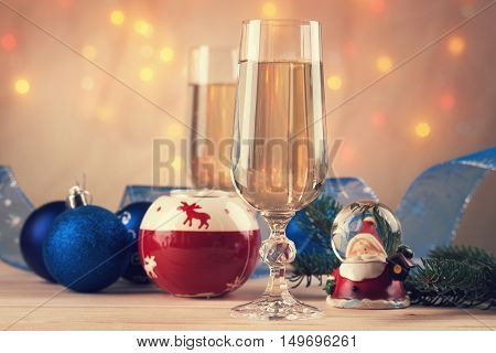 Christmas balls, ribbon, snow globes and champagne on a table