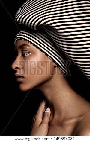 young beautiful fashion model with scarf and makeup on dark background.