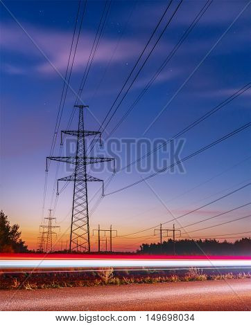 High voltage power lines with electricity pylons at twilight