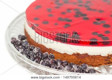 Fragment of layered cake with layers of sponge cake milk jelly and berry jelly and frozen berries on a glass cake serving dish