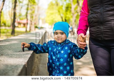 Little baby boy walks in the park with her mother's hand. black boy