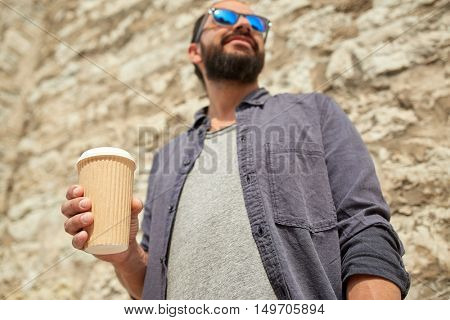 people, drinks, leisure and lifestyle concept - close up of man drinking coffee from disposable paper cup on city street