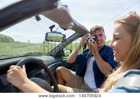leisure, road trip, travel and people concept - happy couple driving in cabriolet car and taking picture by film camera