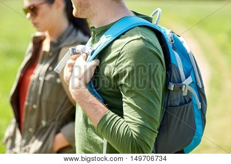 travel, hiking, backpacking, tourism and people concept - close up of couple with backpacks walking outdoors