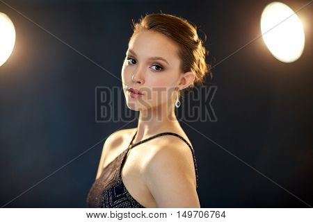 beauty, jewelry, night life, people and luxury concept - beautiful asian woman with diamond earring over black background and spotlights