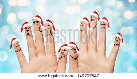 christmas, family, holidays, people and body parts concept - close up of two hands showing fingers in santa hats with smiley faces over blue lights background