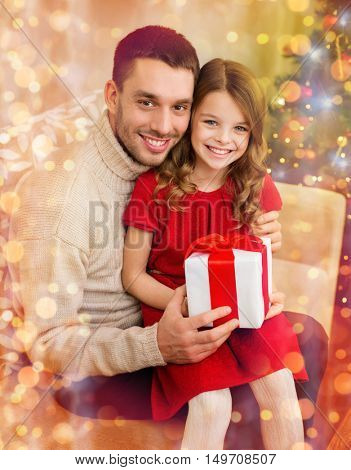family, christmas, x-mas, winter, happiness and people concept - smiling father and daughter holding gift box