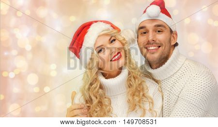 people, christmas, holidays and new year concept - happy family couple in sweaters and santa hats hugging over holidays lights and snow background