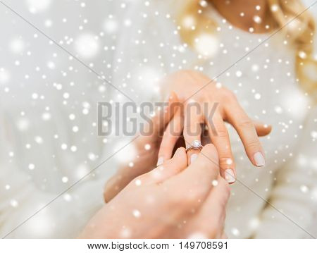 love, couple, relationship and holidays concept - close up of man giving diamond ring to woman