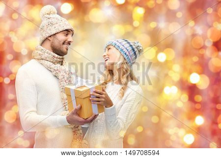 winter, holidays, couple, christmas and people concept - smiling man and woman in hats and scarf with gift box over lights background