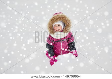 childhood, fashion, season and people concept - happy little kid or girl in winter clothes playing with snow