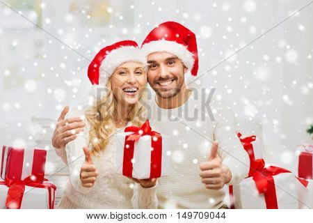 christmas, holidays and people concept - happy couple in santa hats with gift boxes sitting on sofa and showing thumbs up at home
