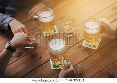 people, leisure and drinks concept - close up of male hands with beer mugs and peanuts at bar or pub