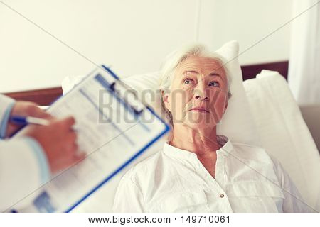 medicine, age, health care and people concept - doctor with clipboard visiting senior woman at hospital ward