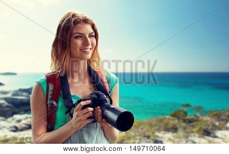 adventure, travel, tourism, hike and people concept - happy young woman with backpack and camera photographing over seashore or beach background