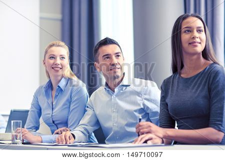 business, people and teamwork concept - group of smiling businesspeople meeting on presentation in office