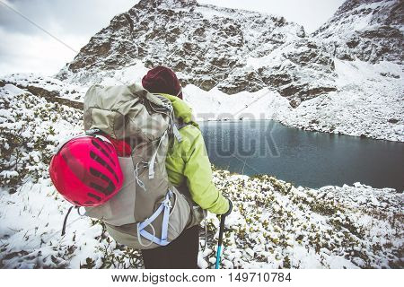 Woman Traveling with backpack hiking Lifestyle adventure concept snow rocky mountains and lake on background winter vacations