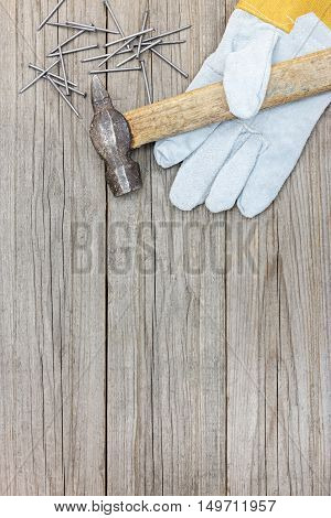 Grey Wooden Background With Old Hammer, Nails And Working Gloves For House Repair And Construction