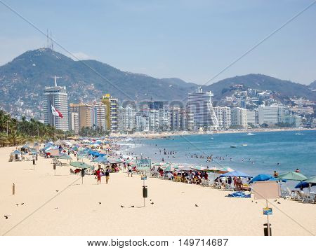 ACAPULCO MEXICO - MARCH 11 2006 : People on the beach with a view of city skyscrapers in Acapulco Mexico.
