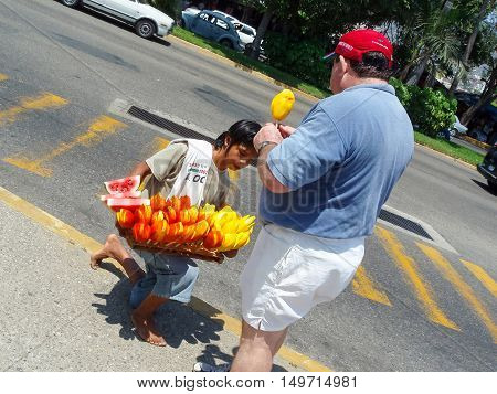 ACAPULCO MEXICO - MARCH 11 2006 : A Mexican boy selling fruit on a stick to a man in the street in Acapulco Mexico.