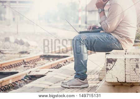 Business man sitting with a laptop in a train station.Photographed side by customizing vintage tone
