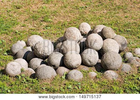 A group of cannonballs in white stone on a green lawn. Milan Italy