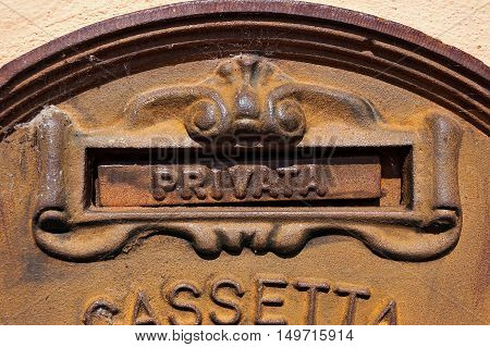 Detail of an Italian old and rusty metal mailbox embedded in a wall with text Privata (Private). Veneto Italy