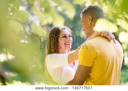 Young woman embraces her boyfrienf around neck outdoor in nature