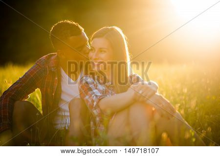 Man kissing woman on cheek outdoor in evening nature at sunset